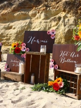 wooden calligraphy signs on crates on the beach