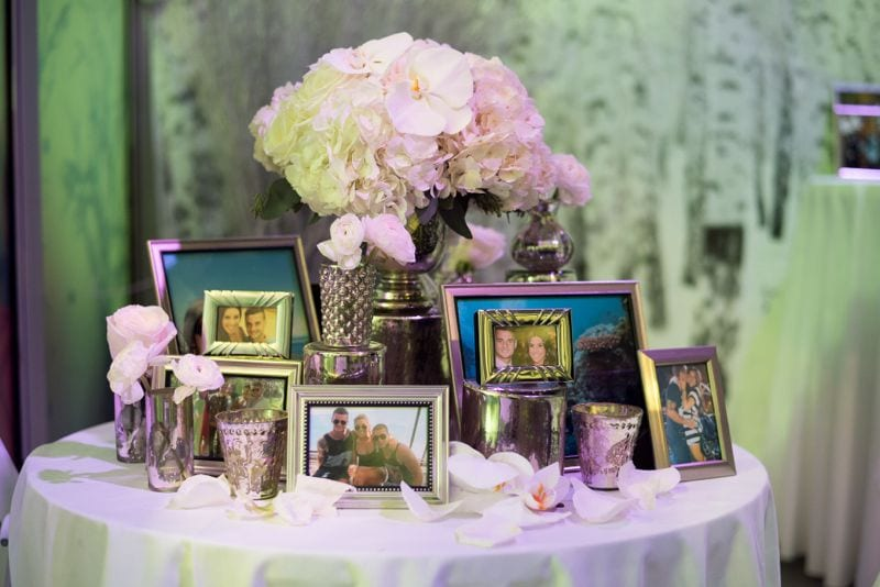 white floral arrangement with pictures on table