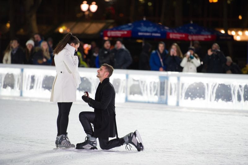 Man down on one knee proposing on ice rink