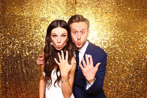 bride and groom in front of gold sparkle backdrop