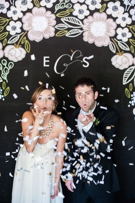 bride and groom blowing confetti at camera