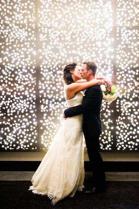 christmas lights backdrop bride and groom kissing