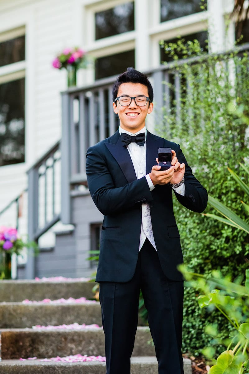 asian man holding out engagement ring