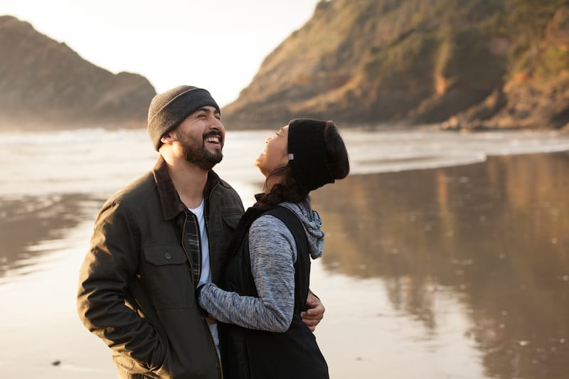 engaged couple laughing on the shoreline