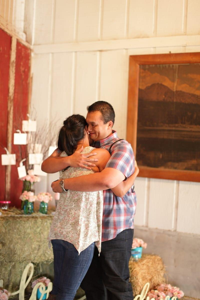 wedding proposal in barn with hay barrels
