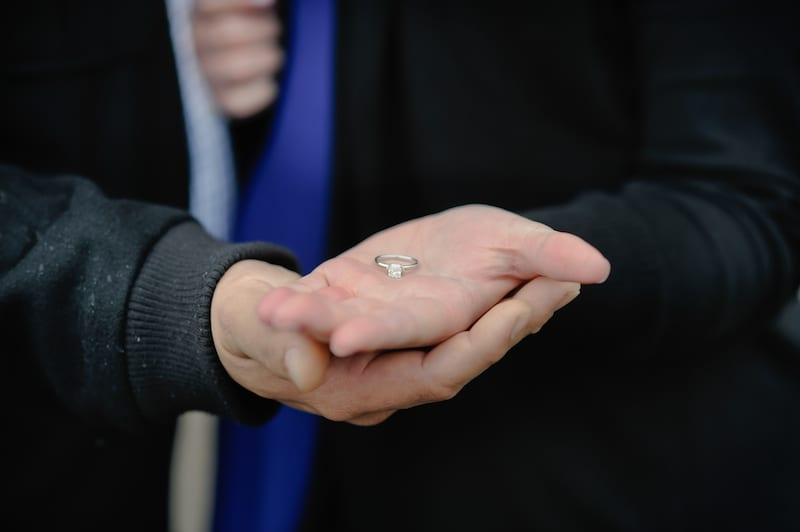 solitaire engagement ring in couples hands
