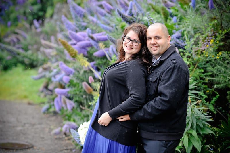 man and woman in front of purple flowers