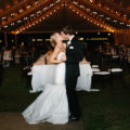 bride and groom kissing under wedding tent