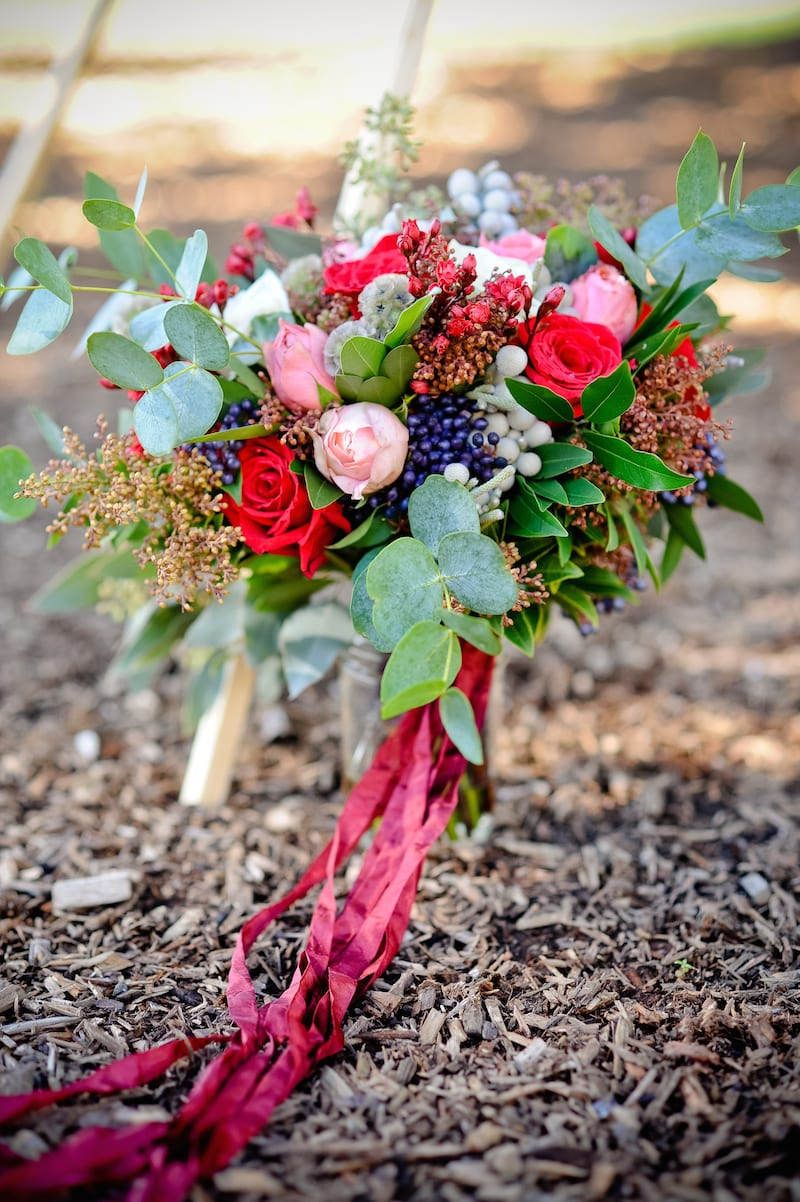 lush bridal bouquet tied with maroon ribbon