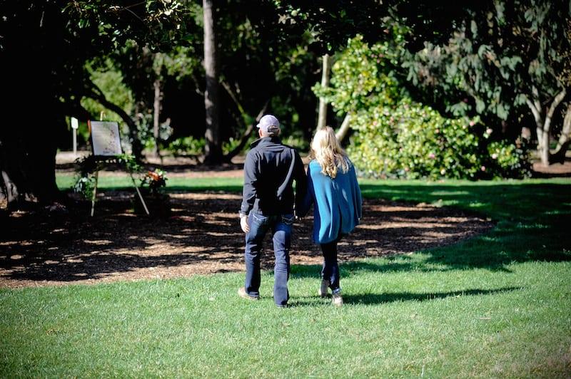 couple walking towards marriage proposal under tree