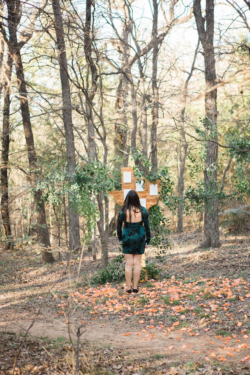 girl reading notes on sign in wooded area