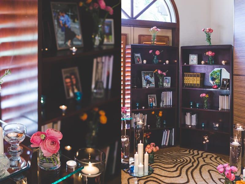 ranunculus and candles proposal decor on bookshelves