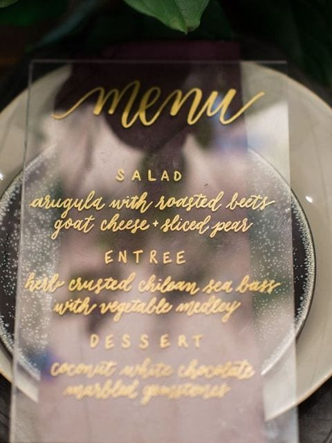 gold calligraphy menu on acrylic