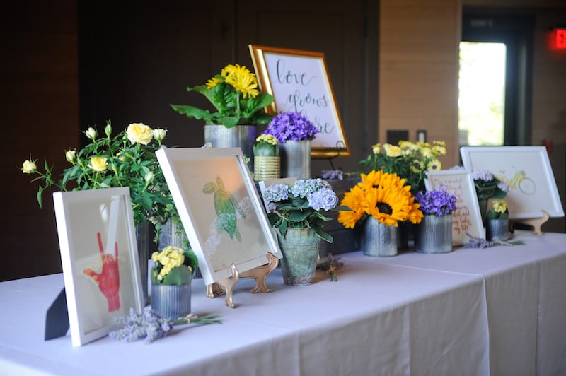 table covered with flowers and framed paintings