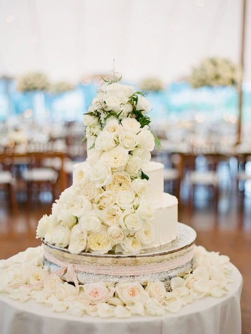 cascading white flowers on white wedding cake