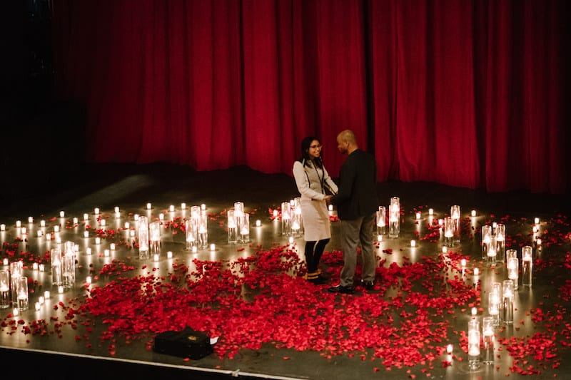 red roses and candles on stage proposal