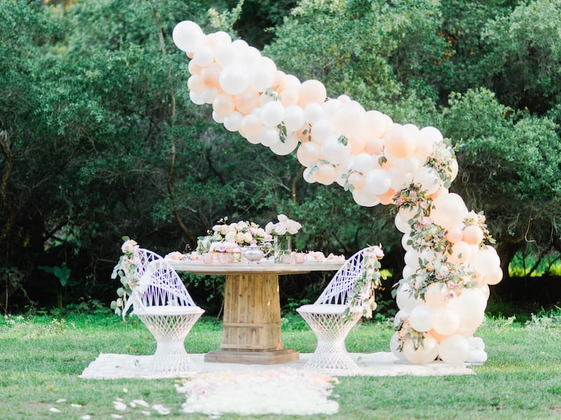 a-symetrical balloon arch over picnic for two