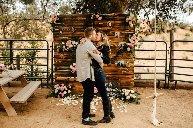rustic wooden wall backdrop with flowers and printed pictures