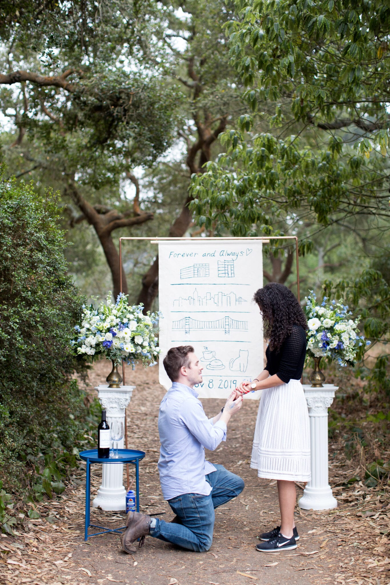 man proposing in front of banner and blue florals