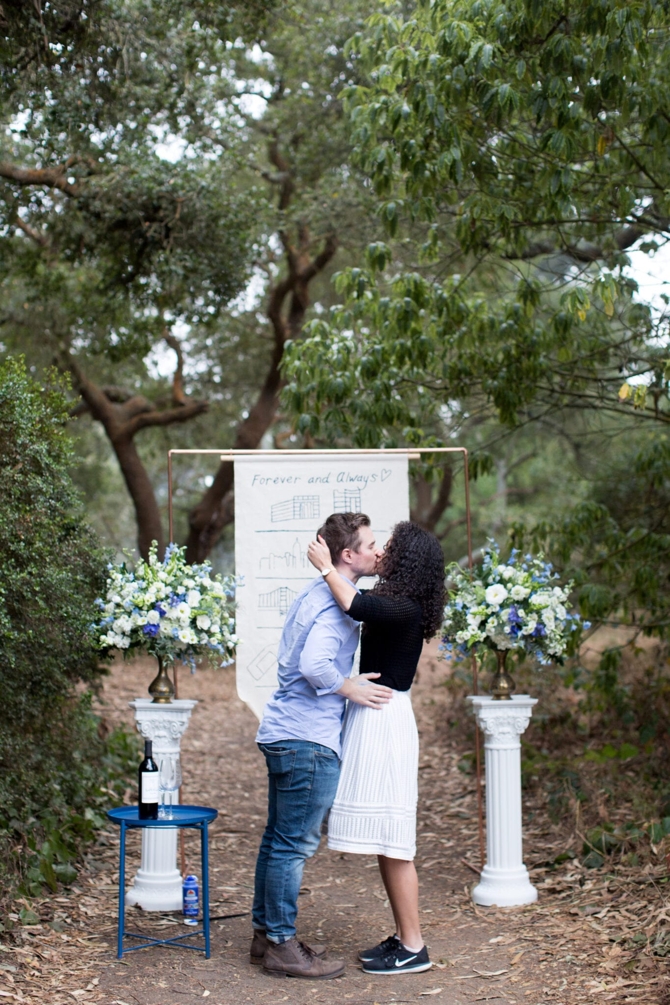 engagement in front of copper arch and pillars with blue flowers
