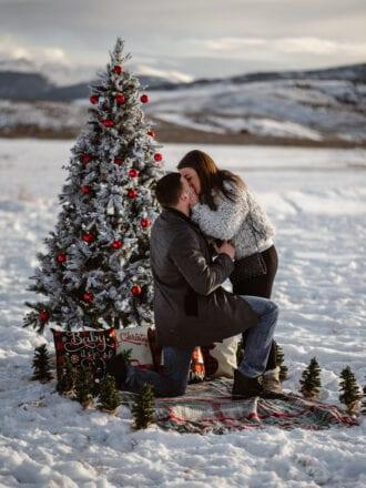 man and woman kissing at christmas marriage proposal in utah
