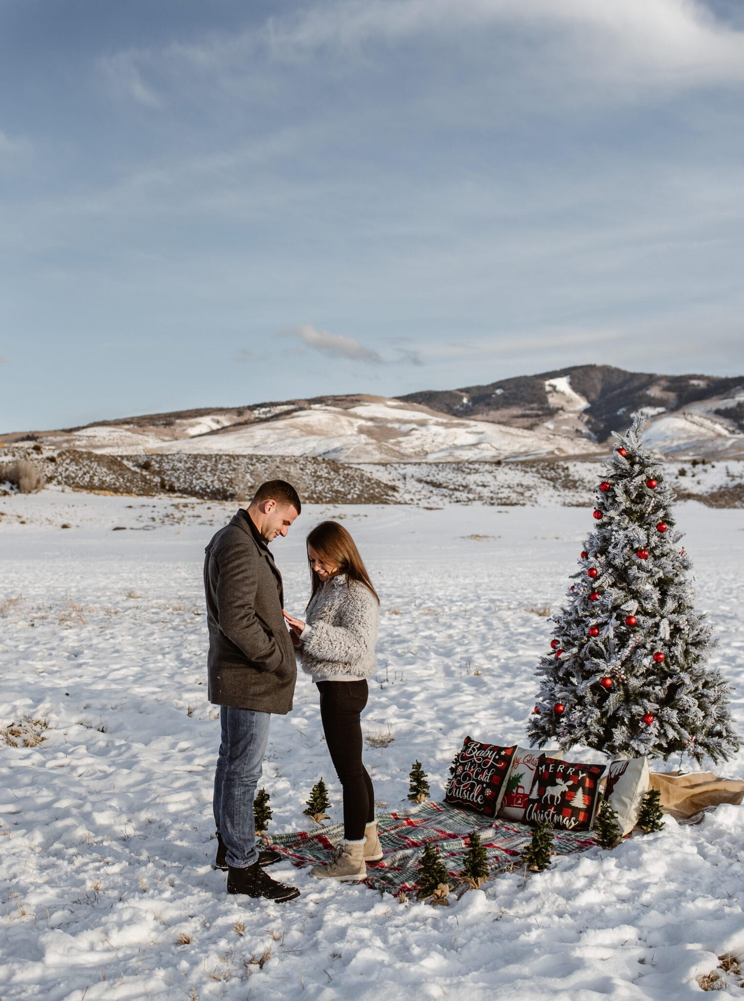 engagement in the snow with christmas tree