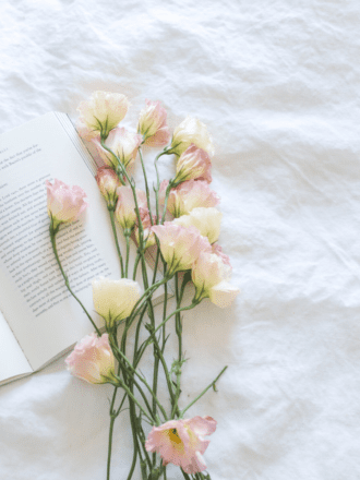 Book and flowers on bed