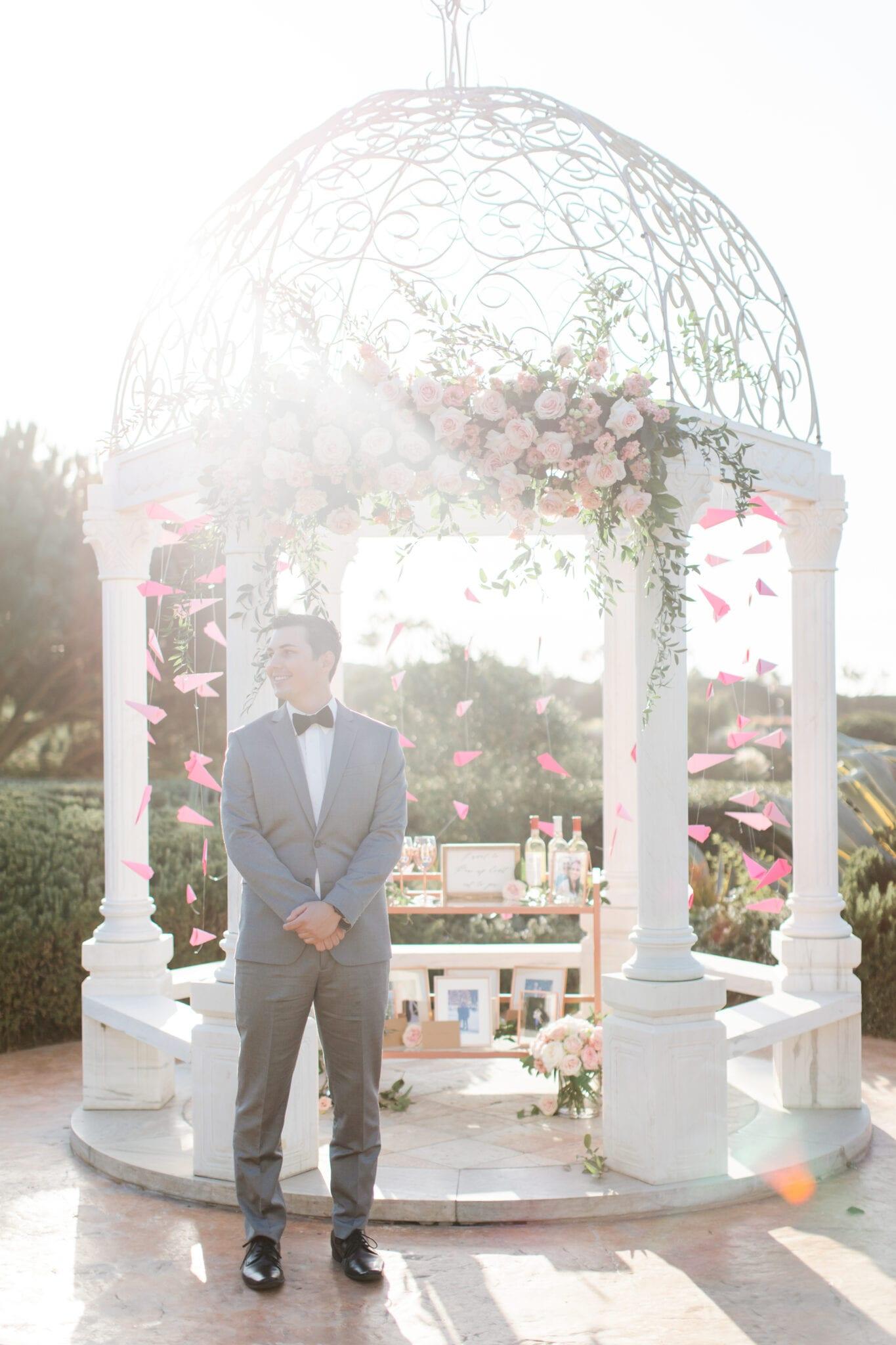 man waiting in front of wedding proposal gazebo