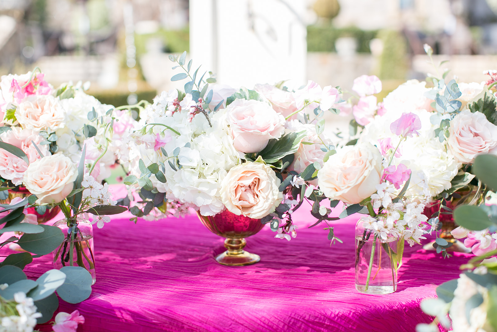 gold vases with pink flowers with pink table