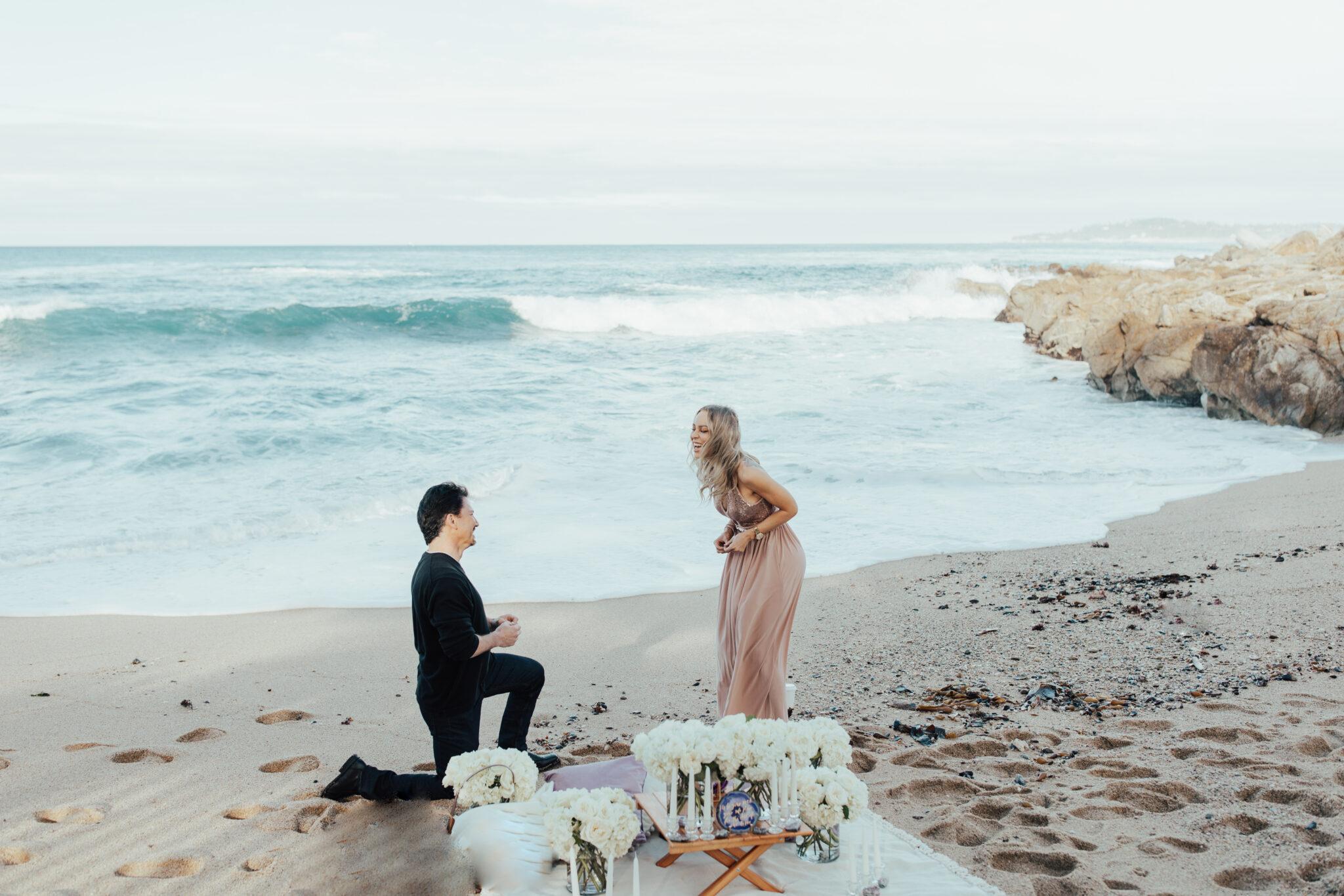 man proposing in sand