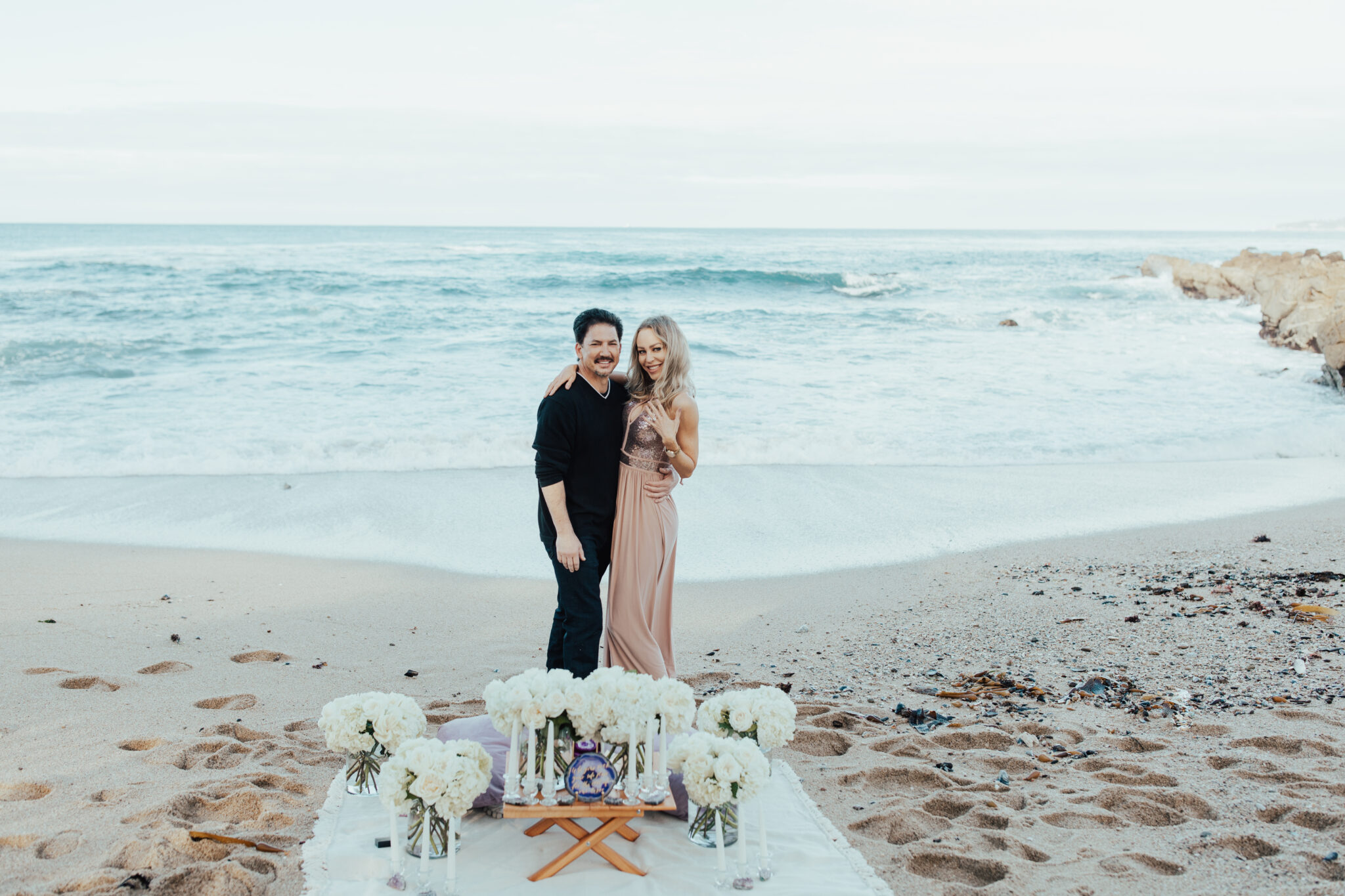 couple getting engaged by the beach