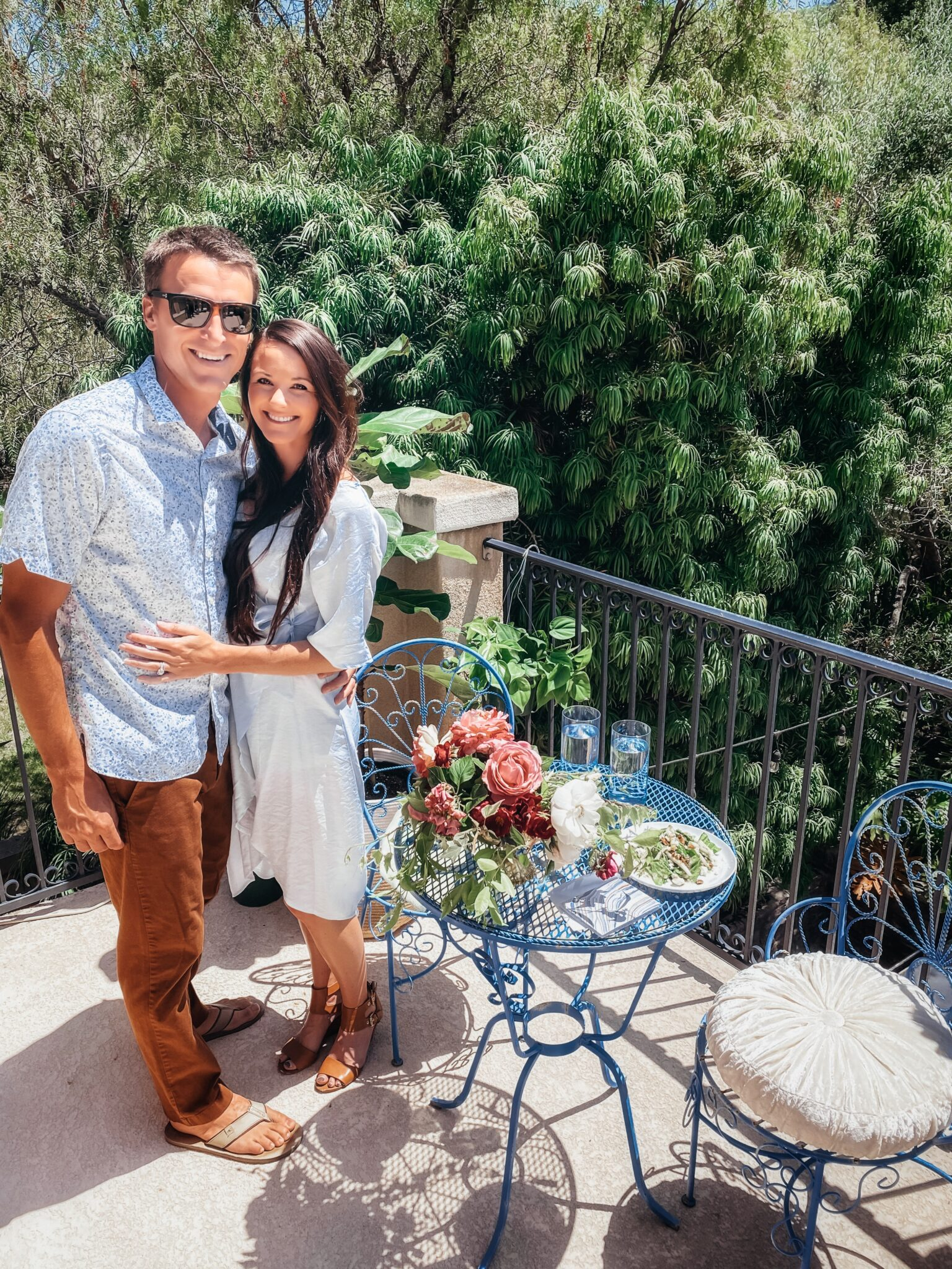 couple standing next to table on balcony