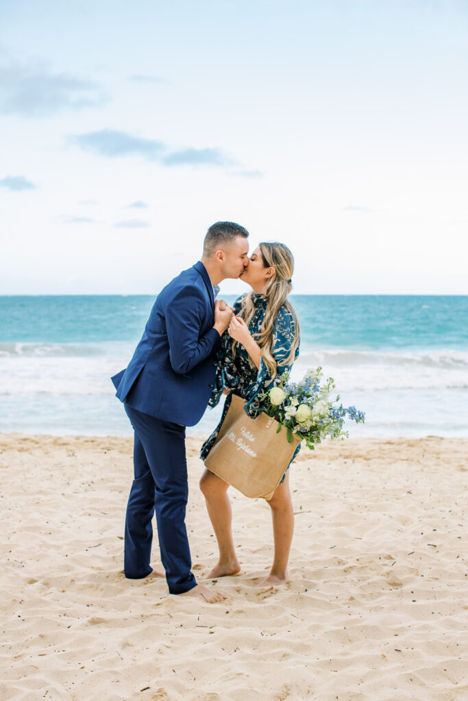 Couple kissing on beach after getting engaged