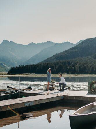 man proposing to girlfriend on lake