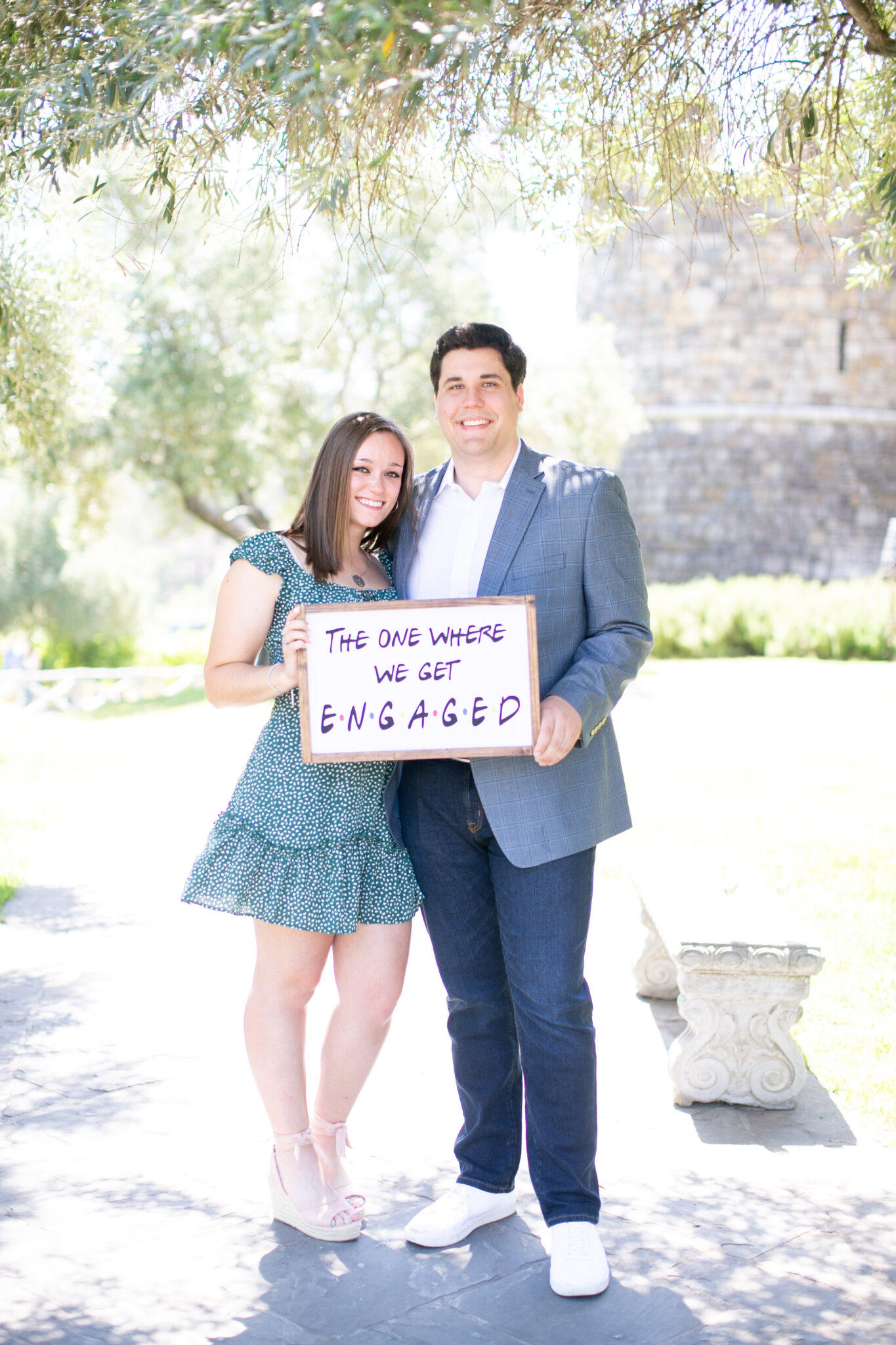 Couple holding friends themed sign after engagement