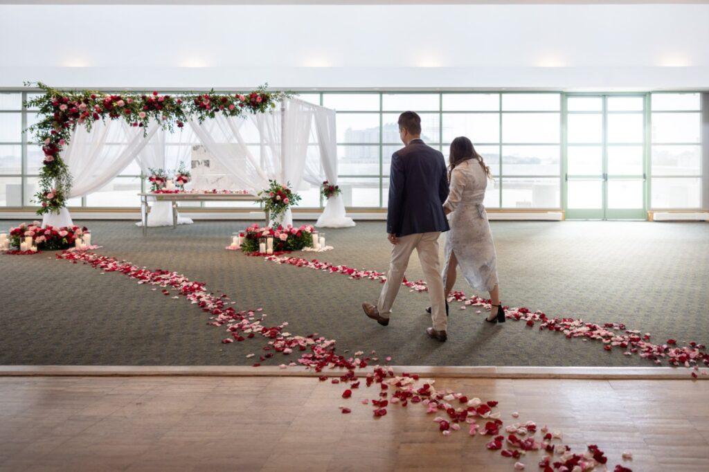 couple walking towards red rose backdrop