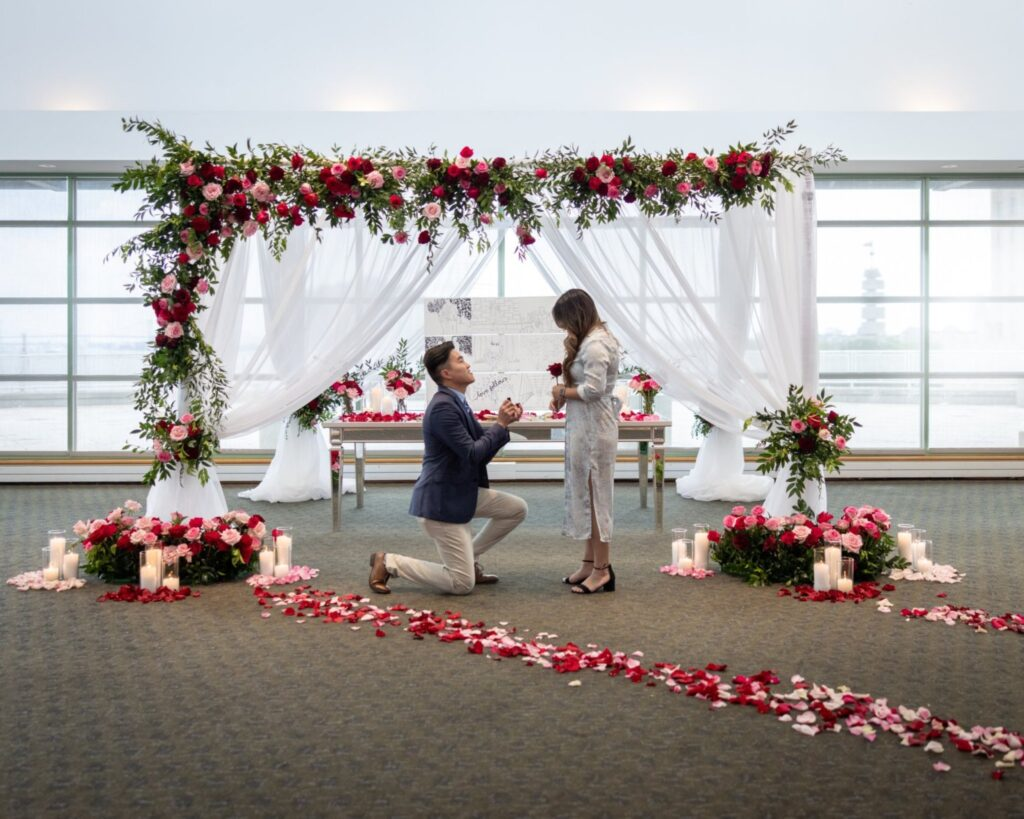 man down on one knee in front of red rose backdrop