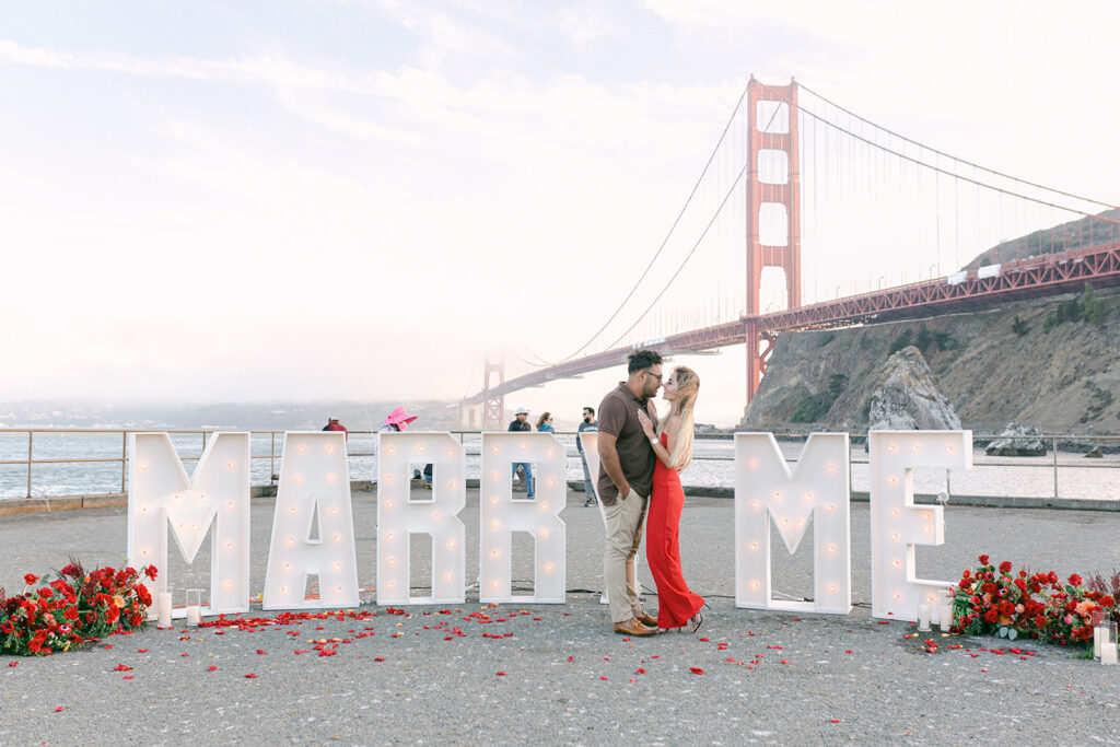 couple getting engaged in front of golden gate bridge