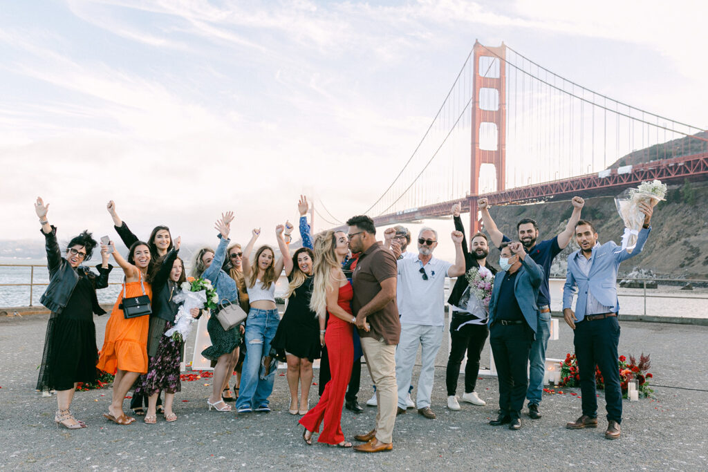 Family and friends celebrating proposal in front of golden gate bridge