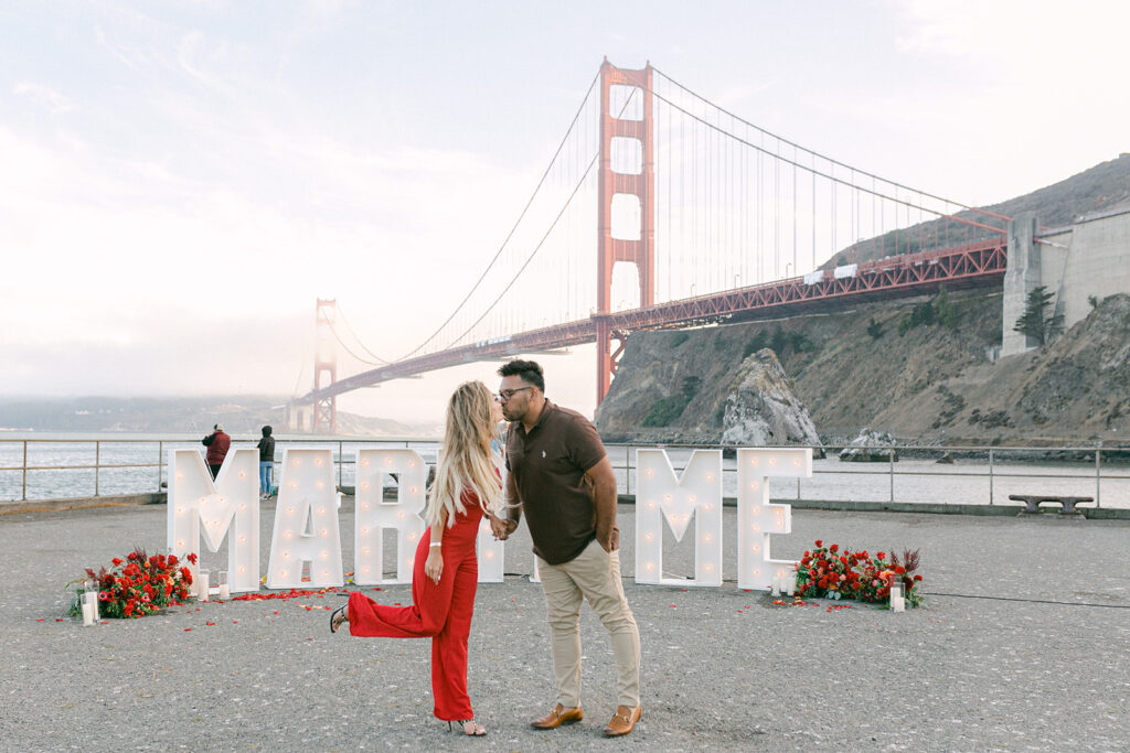 couple kissing in front of golden gate bridge