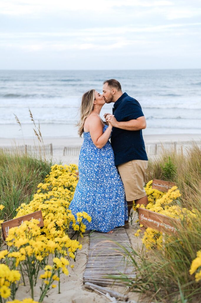 couple kissing in yellow daisies