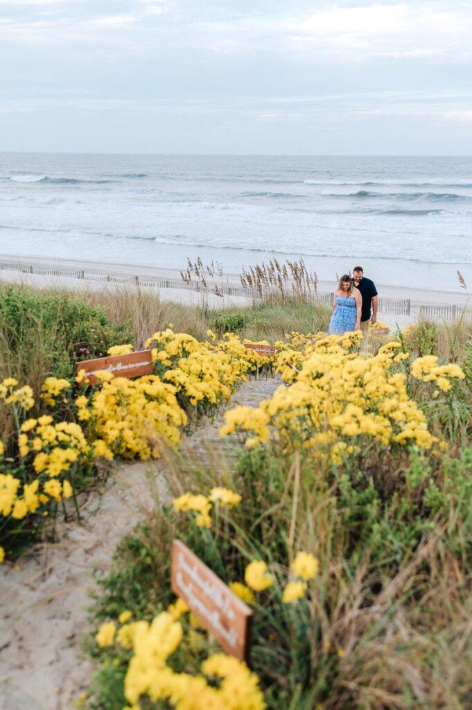 couple walking up yellow daisy walkways